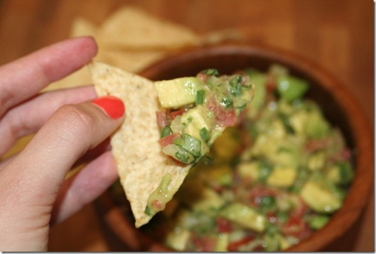 Tortilla chip dipped in guacamole